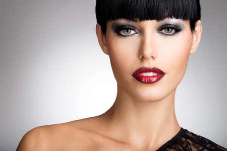 labios sexy: Hermosa mujer con los labios rojos atractivos y maquillaje de ojos color de moda. Primer retrato de un modelo femenino.