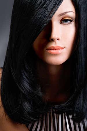 capelli dritti: Bella donna bruna con lunghi capelli lisci neri in posa in studio LANG_EVOIMAGES