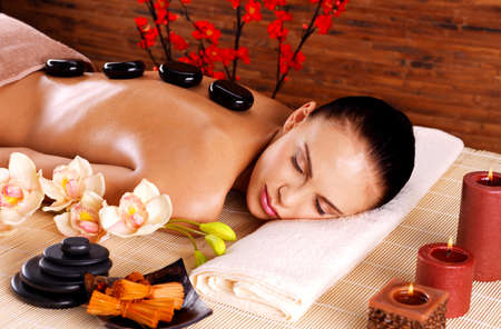 Adult woman relaxing in spa salon with hot stones on back. Beauty treatment therapy LANG_EVOIMAGES