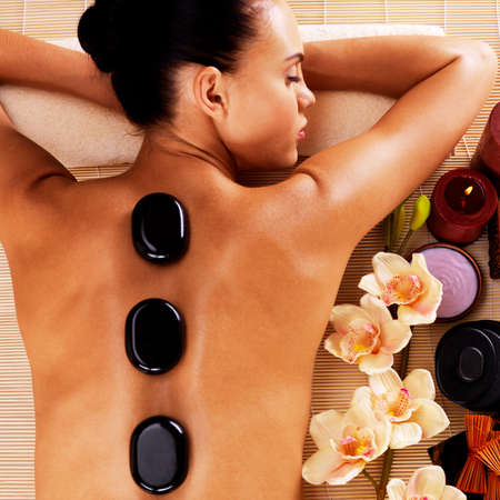 hot stone massage: Adult woman relaxing in spa salon with hot stones on body. Beauty treatment therapy
