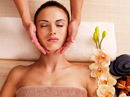 face massage: Masseur doing massage the head of an adult woman in the spa salon