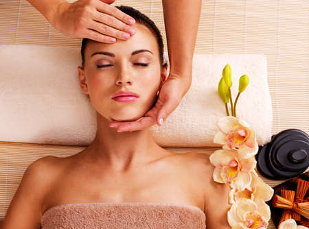 head massage: Masseur doing massage the head of an adult woman in the spa salon