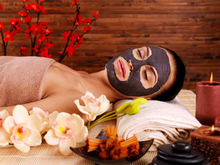 resting mask: Adult woman relaxing in spa salon. Female face with cosmetic mask. Beauty treatment