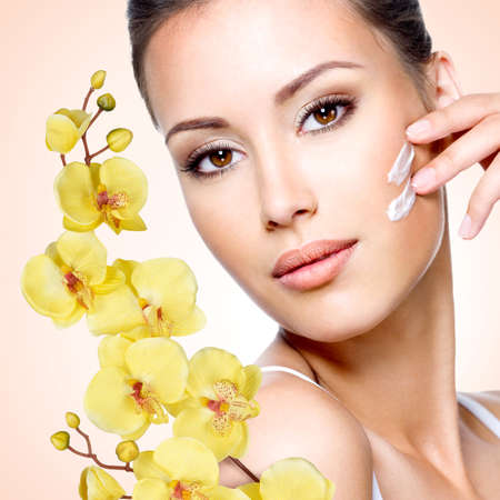 moisturize: Woman applying cosmetic cream on the face