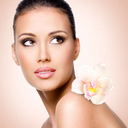 clear skin: Face of beautiful woman with health skin and  flower over art background