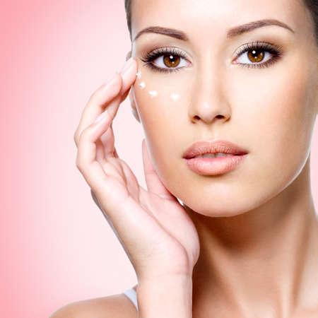 Portrait de femme avec le visage sain appliquer une crème cosmétique sous les yeux