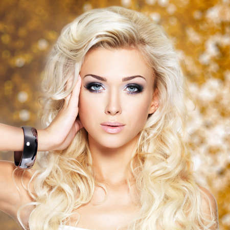 Portrait of a beautiful blond woman with long curly hair and dark makeup.  Stock Photo