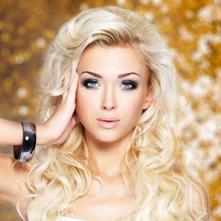 vrouw blond: Portret van een mooie blonde vrouw met lang krullend haar en donkere make-up.