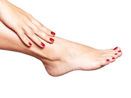 over white background: Closeup photo of a female feet with beautiful red pedicure over white background