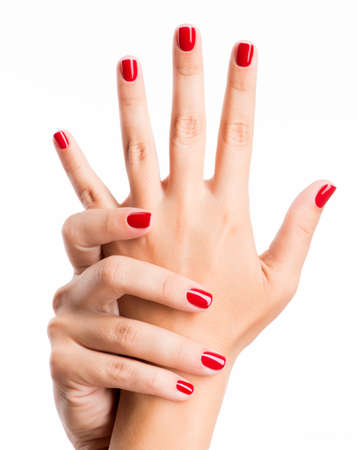 nails: Closeup photo of a beautiful female hands with red nails isolated on white background LANG_EVOIMAGES