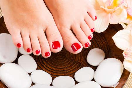 pedicure: Closeup photo of a beautiful female feet with red pedicure