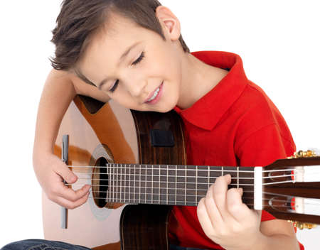 a guitarist boy playing guitar: Smiling caucasian boy is playing the acoustic guitar - isolated on white background LANG_EVOIMAGES