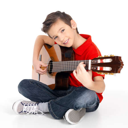 boy playing guitar: Handsome happy  boy is playing on acoustic guitar - isolated on white background LANG_EVOIMAGES