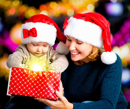 Mother with little child opens the box with gifts on the christmas holiday - indoors Stock Photo - 23852704