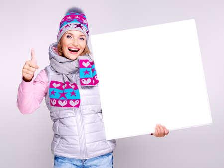 outerwear: Donna sorridente esterno in inverno detiene il banner con pollice in alto segno LANG_EVOIMAGES