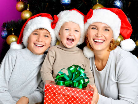 Happy mother with children holds the new year gift on the christmas holiday - indoors Stock Photo - 23503452