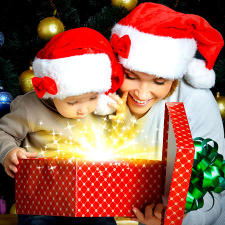 Mother with little child opens the box with gifts on the christmas holiday - indoors Stock Photo - 23503453