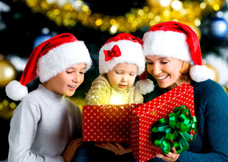 baby open present: Mother with children opens the box with gifts on the christmas holiday - indoors