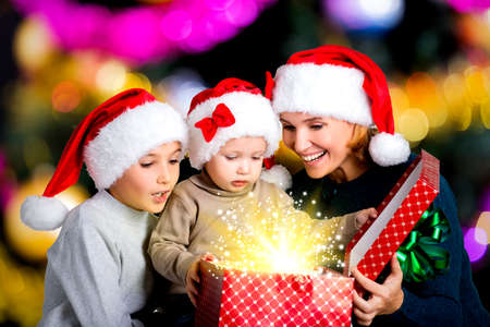 baby open present: Mother with happy children opens the box with christmas gifts on the new year  holiday - indoors