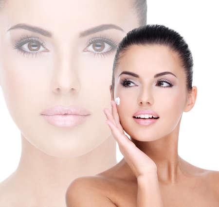 Jonge vrouw met cosmetische crème op een mooi vers gezicht - geïsoleerd op wit