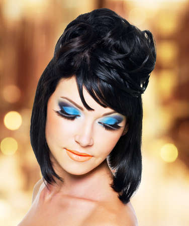 Face of a beautiful young woman with brightly blue makeup photo