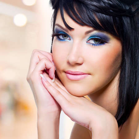 Beautiful young woman with brightly blue make-up photo