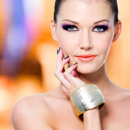 Fashion portrait of the beautiful woman with black nails and makeup photo