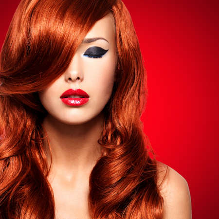 curly hair model: Portrait  of beautiful  woman with long red hairs and red lips. Calm face  of adult pretty girl