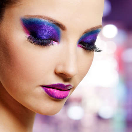 Beautiful female face with bright purple fashion makeup  Stock Photo