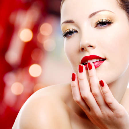 Femme sexy avec maquillage or et manucure rouge