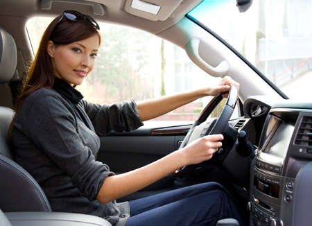 inside car: beautiful young happy woman posing inside of  the new car