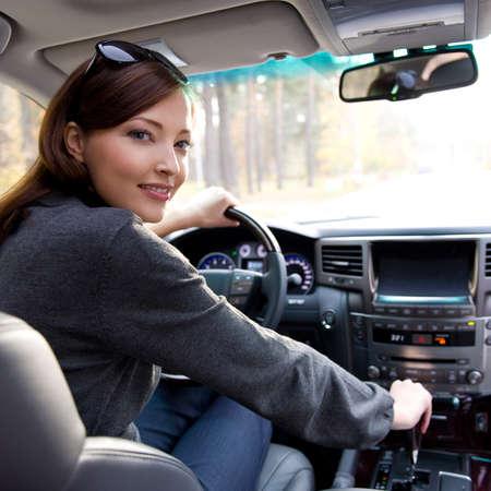 Portrait de belle jeune femme dans la nouvelle voiture - plein air