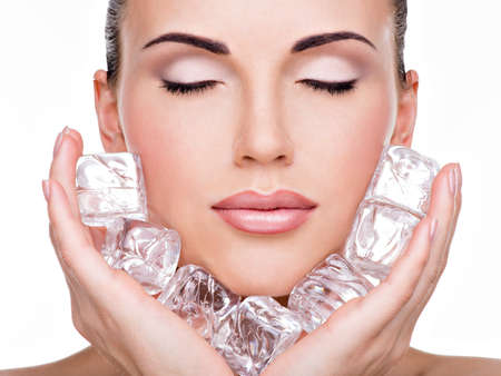Beautiful young woman applies the ice to face. Skin care concept.  LANG_EVOIMAGES