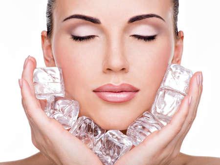 Belle jeune femme se applique la glace à face. concept de soins de la peau.