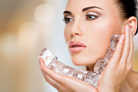 Beautiful young woman applies the ice to face. Skin care concept.  Banco de Imagens