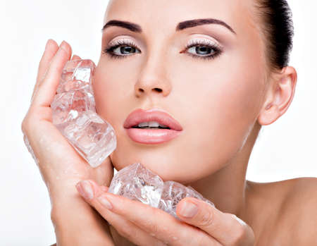cube: Beautiful young woman applies the ice to face. Skin care concept.  LANG_EVOIMAGES