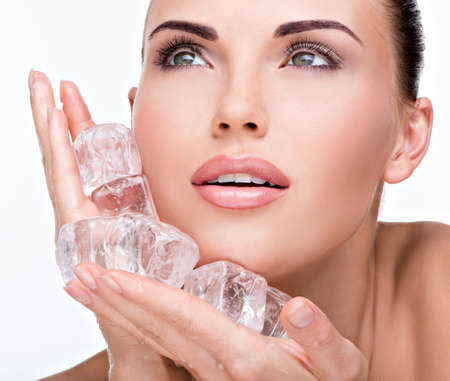 Beautiful young woman applies the ice to face. Skin care concept.  Imagens