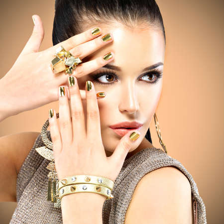 Portrait of the beautiful fashion woman with black makeup and golden manicure LANG_EVOIMAGES