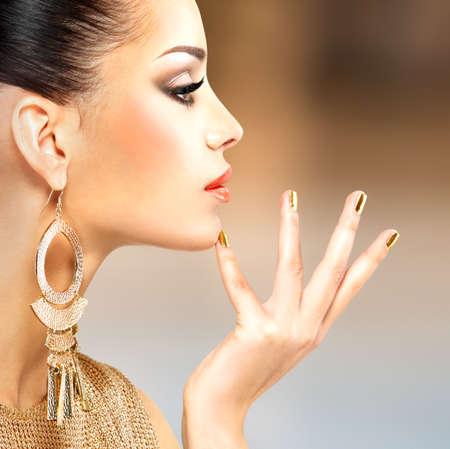 Profiel portret van de mooie mode vrouw met zwarte make-up en gouden manicure