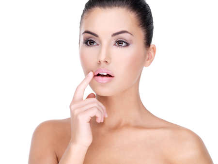Face of a Pretty young woman with finger at  lips - on white background