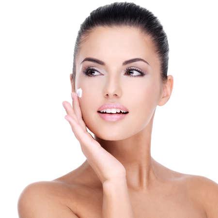fresh face: Giovane donna con crema cosmetica su un bel viso fresco - isolato su bianco