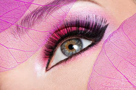 Primo piano dell'occhio femminile con una bella rosa brillante di moda trucco