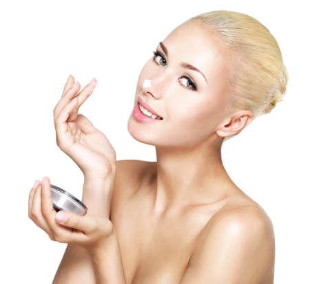 Jeune femme appliquer la crème cosmétique sur le nez - isolé