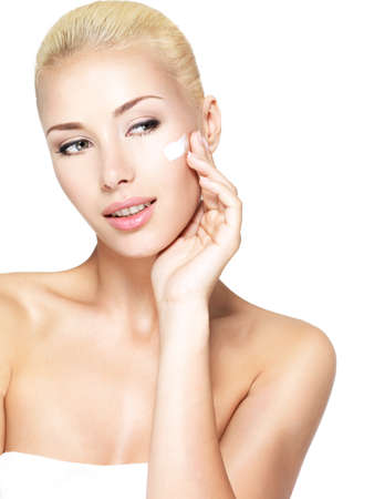 woman face cream: Young woman applying cosmetic  cream on a clean fresh face Stock Photo