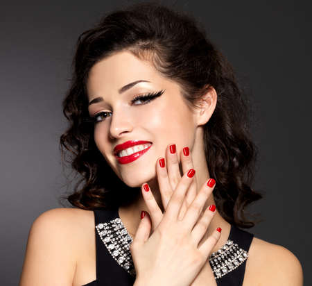 Young pretty woman with red manicure and  lips.  Fashion model with bright positive emotions Stock Photo - 24246434