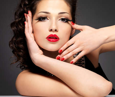 Pretty fashion model with red manicure and lips - Brunette woman on black Stock Photo - 24240781