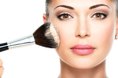 메이크업 브러쉬를 사용하여 얼굴에 건조 화장품 색조 기초를 적용하는 여자의 근접 촬영 초상화.