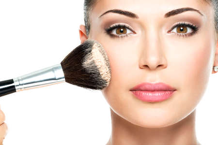 makeup a brush: Closeup portrait of a woman  applying dry cosmetic tonal foundation  on the face using makeup brush.