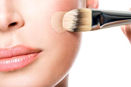 여자의 얼굴에 액체 색조 기초를 적용하는 메이크업 아티스트. 뺨의 근접 촬영 사진
