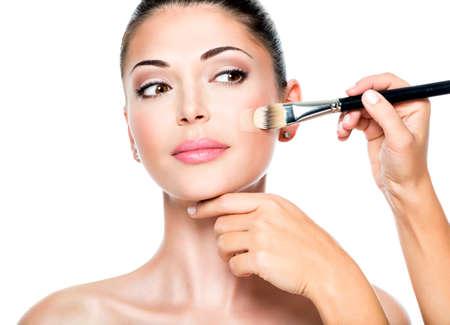 Make-up artist het aanbrengen van vloeibare tonale foundation op het gezicht van de vrouw